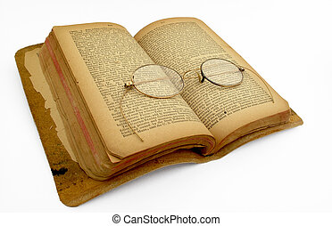 An open book with antiques gold eyeglasses