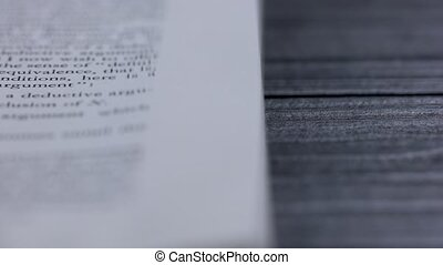 An open book with English text lies on a wooden table. The pages of the book turn over in slow motion. Part of the text is blurry. Close up