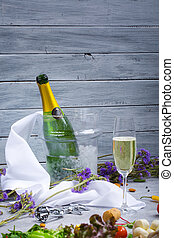 An open bottle of champagne in a bucket with ice, a glass of champagne, silver corkscrew on a light wooden background.
