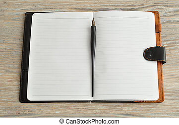An open notebook with a fountain pen displayed on a table