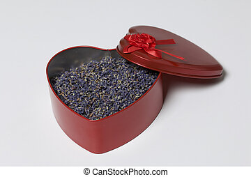 An open red box in the shape of a heart with dried lavender flowers. It stands on a white background.