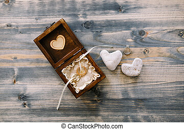 An open wooden box with wedding rings and two heart-shaped pebbles on a gray wood background.