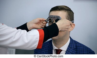 An ophthalmologist is checking a man's vision