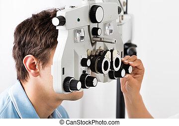 An Optometrist Adjusting Phoropter For Patient