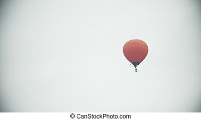 An orange air balloon flying on a background of white sky....