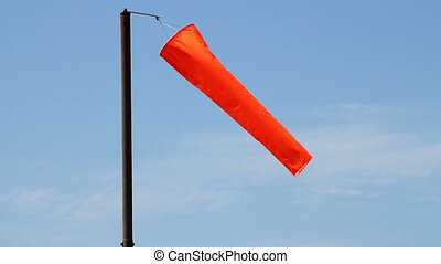 An orange airport windsock, blowing in the wind.