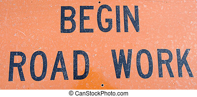 Begin Road Work - An orange and black Begin Road Work sign
