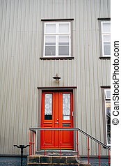 An orange door with glass and curtains in a building with white walls, steps with a handrail and plastic windows.