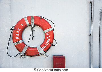 An orange life buoy for safety at sea attached to the cruise ship