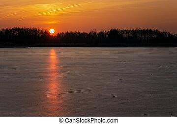 An orange sunset over a frozen lake