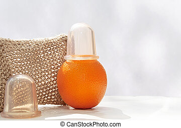 An orange with a vacuum can at the top is on the table against the backdrop of a mesh washcloth made from natural fibers