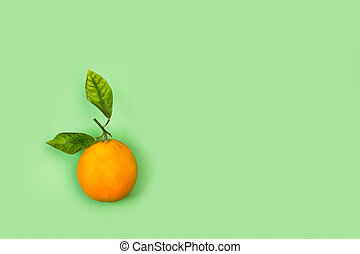 An orange with leaves on a green background