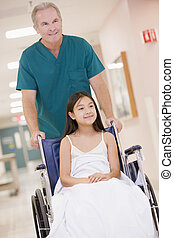 An Orderly Pushing A Little Girl In A Wheelchair Down A Hospital Corridor
