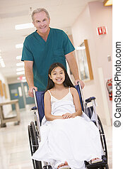 An Orderly Pushing A Little Girl In A Wheelchair Down A...