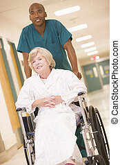 An Orderly Pushing A Senior Woman In A Wheelchair Down A...