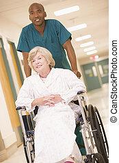 An Orderly Pushing A Senior Woman In A Wheelchair Down A Hospita