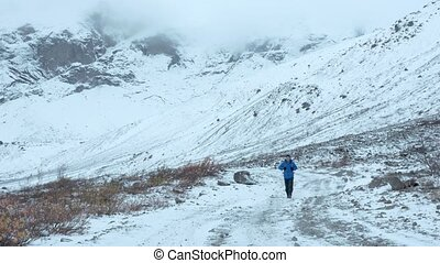 An ordinary middle-aged man traveling on mountain routes. He goes on a snowy road alone.