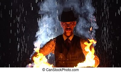 An original performance by a fire tamer with burning torches in the pouring rain. A male artist looms in the light of fire and smoke against a dark studio background. Fire show. Close up. Slow motion