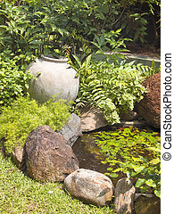 an ornamental garden with decorative pot and tropical plants