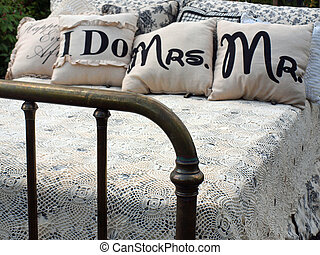 An Outdoor Bed with Lacey Blankets and Wedding Pillows