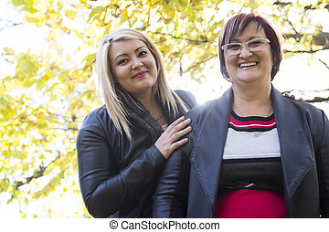 Outdoor portrait of caucasian senior mother with her adult daughter