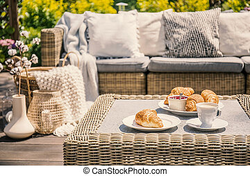 An outdoor wicker table and a sofa with cushions. Croissants for breakfast on a patio on a summer morning in an exclusive apartment with garden during vacation.