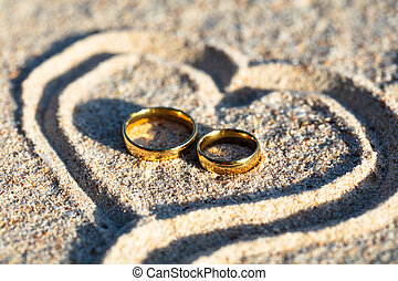 Golden Wedding Rings Inside The Heart Shape On Sand - An ...