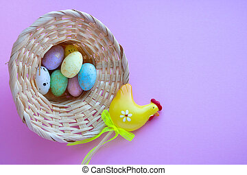 An overturned basket in the shape of a hat with eggs on a pink background. Easter Concept. Space for your text