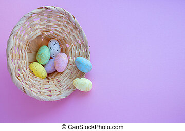 An overturned basket in the shape of a hat with eggs on a pink background. Easter Concept