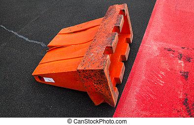 An overturned safety barrier. - An overturned orange safety ...