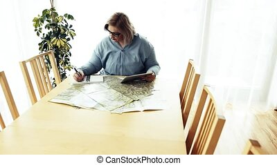 An overweight woman at home, sitting at the table with...