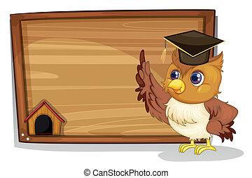 An owl wearing a graduation cap beside a wooden board