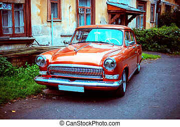 an retro orange car parked in front of a house