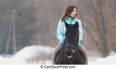An smiling young woman on a horseback in a winter forest