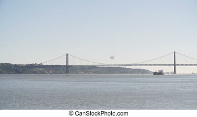 An ultra-wide shot of 25 de Abril Bridge in Lisbon, Portugal with boats and ferries going past on a sunny day with blue sky.