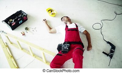 An unconscious man worker lying on the floor after accident...