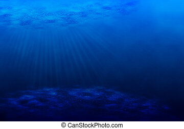 An underwater scene with sun rays shining through the water's glittering and moving surface.