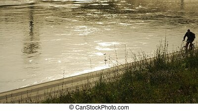 An unidentified cyclist cycles along the riverbank. - An...