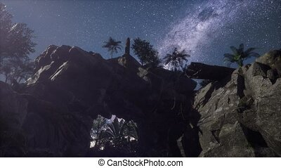 An unrealistic night landscape through a cave with milky way
