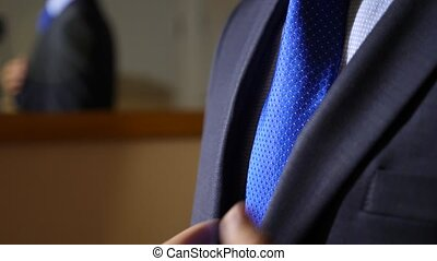 An unrecognizable businessman, puts the phone in the inner pocket of his jacket. 4k, slow motion