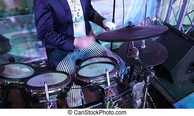 An unrecognizable drummer in a jacket, a man playing drums, a drummer in a music band, a live performance. Anonymous Drummer Drumming on Stage - Close Up