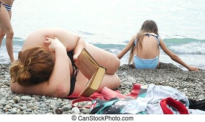 an unrecognizable fat woman lies on the beach and reads a...
