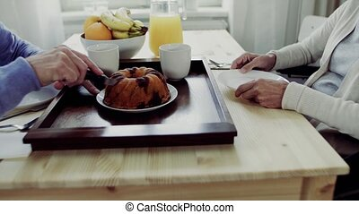 An unrecognizable senior couple sitting at the table at home, having breakfast.