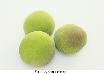 an unripe ume [plum] - Group of fresh green plum on white...