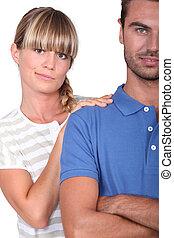 An unsure woman touching her husband's shoulder