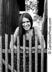An young woman with near the wooden fences in the village. Black and white photo.