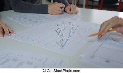 analisi, e, discussione, di, grafici, su, tavola, maschio femmina, mano, con, uno, pencil.