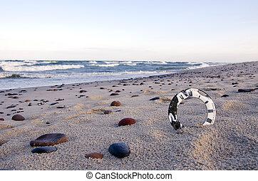 analog aged clock face on sea beach sand