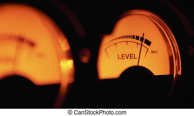 Analog Dial Indicator of Sound Signal Level in db. Arrow moves in sync with sound level. Close-up. Analog VU meter. Professional studio equipment. Classic vintage volume indicator working Reel to reel VU meters.