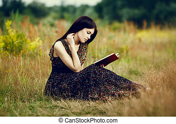 Artistic portrait of young gorgeous brunette on green meadow with book. Shallow depth of field